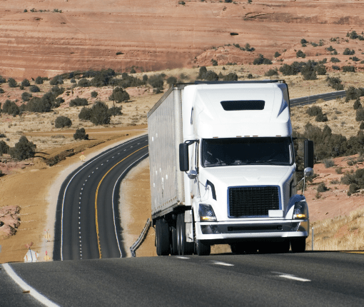 large semi-truck driving on a desert highway